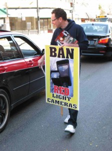 Citizens to Abolish Red Light Cameras member Scott Davis hands out fliers at a protest last summer.