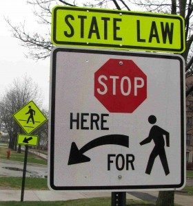 A sign in Evanston reminds drivers to stop when pedestrians are present.