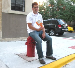 Mike Stephen sits atop his nemesis--the fire hydrant.