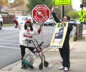 Two anti-speed camera protestors wave to supportive drivers Saturday on Foster Avenue adjacent to Gompers Park.