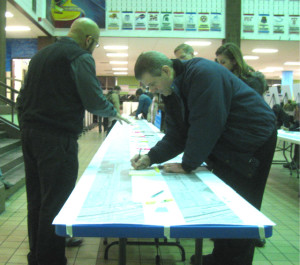 Attendees of the Ashland BRT Open House Tuesday night write thoughts on a large map of the proposed route.