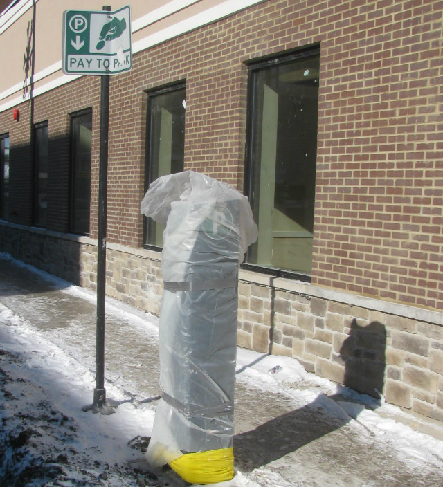 A parking meter pay box bundles up from the cold on North Avenue.