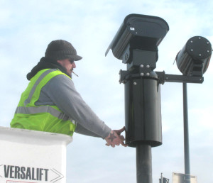A technician for Xerox, fearing industrial espionage, covers up the casing to a new red light camera being installed at Elston and Addison.
