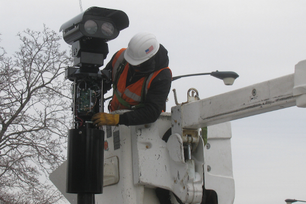 A Xerox contractor installs a red light camera at the corner of Clark Street and Irving Park Road.