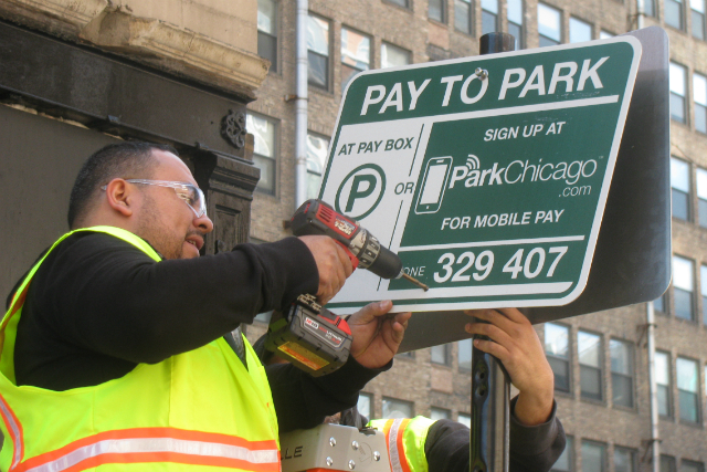 Workers for CPM erect one of the 42,000 signs needed citywide for the ParkChicago mobile pay to park system.