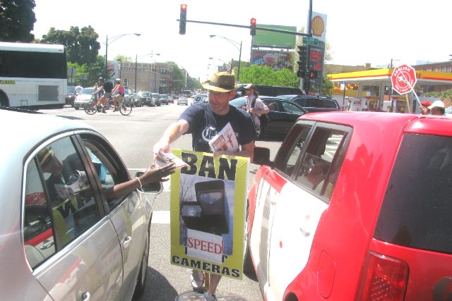 Scott Davis hands out anti-red light camera fliers to interested drivers at a summer protest.