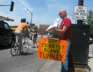 Jeff Black (foreground) and Scott Davis (background) pass out fliers attacking Ald. Tom Tunney (44th) for supporting speed cameras at a protest earlier in the summer.