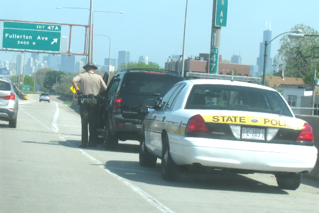 An Illinois STate Trooper converses with a driver caught riding on the shoulder of the Kennedy Expressway recently.