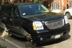 A car in Lincoln Park is still ticketed for a street cleaning violation even after getting all four wheels stolen. Photo: DNA Info.com