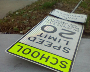 A school zone speed limit sign lays on the pavement near a school on the city's north side.